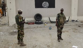 Chadian soldiers stand at a checkpoint in front of a Boko Haram flag in the Nigerian city of Damasak, Nigeria, Wednesday March 18, 2015. Damasak was flushed of Boko Haram militants last week, and is now controlled by a joint Chadian and Nigerien force. (AP Photo/Jerome Delay) ** FILE **