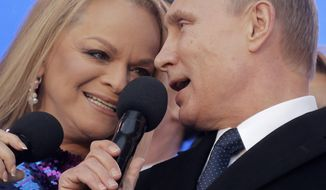 "Russian President Vladimir Putin and singer Larisa Dolina sing the national anthem at a rally marking the one year anniversary of annexation of Ukraine's Crimea peninsula, outside the Kremlin in  Moscow, Russia, Wednesday, March 18, 2015. Speaking to tens of thousands of supporters just outside the Kremlin walls, President Vladimir Putin has described Russia's annexation of Ukraine's Crimean Peninsula as a move to protect ethnic Russians and regain the nation's ""historic roots."" (AP Photo/Maxim Shipenkov, Pool)"