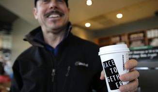 "Matt Ullman holds a coffee drink with a ""Race Together"" sticker on it at a Starbucks store in Seattle, Wednesday, March 18, 2015. Starbucks CEO Howard Schultz announced earlier in the day at the company's annual shareholder meeting that participating baristas at stores in the U.S. will be putting the stickers on cups and also writing the words ""#RaceTogether"" for customers in an effort to raise awareness and discussion of race relations. (AP Photo/Ted S. Warren)"