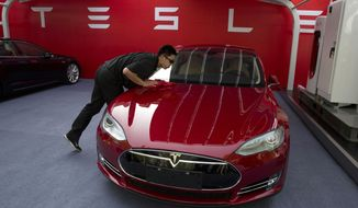 FILE - In this April 22, 2014 file photo, a worker cleans a Tesla Model S sedan before a event to deliver the first set of cars to customers in Beijing. Tesla Motors on Thursday, March 19, 2015 said it is updating its Model S electric car to help ease drivers' worries about running out of battery charge.  (AP Photo/Ng Han Guan, File) **FILE**