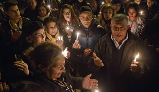 "Tunisians holding candles pray at the entrance gate of the National Bardo Museum where scores of people were killed after gunmen staged an attack, Tunis, Wednesday, March 18, 2015. Foreign tourists scrambled in panic Wednesday after militants stormed a museum in Tunisia's capital and killed scores of people, ""shooting at anything that moved,"" a witness said. (AP Photo/Michel Euler)"