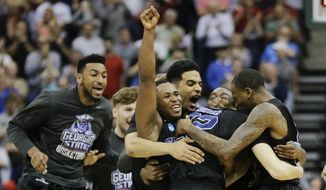 Georgia State players celebrate as they surround R.J. Hunter (22 after he made the game-winning shot against Baylor late in the second half in the second round of the NCAA college basketball tournament, Thursday, March 19, 2015, in Jacksonville, Fla.   Georgia State won 57-56. (AP Photo/Chris O'Meara)