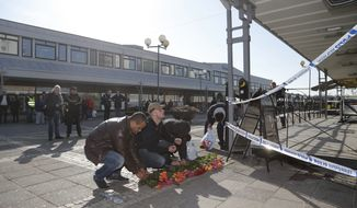 People placing  flowers at the crime scene of  a fatal shooting in Gothenburg, Sweden, Mach 18, 2015. Two people were killed and several injured when at least one gunman armed with automatic weapons fired into a pub in Gothenburg in western Sweden, in what the police decribed as agang related assault.  (AP Photo / ADAM IHSE  / TT)   **  SWEDEN OUT  **