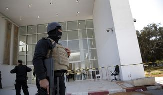 Policemen guard the entrance of the Bardo museum in Tunis, Tunisia, Thursday, March 19, 2015, as a a blood stain is seen at right, a day after gunmen opened fire killing over 20 people, mainly tourists. (AP Photo/Christophe Ena)