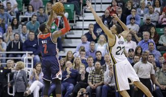 Washington Wizards guard John Wall (2) shoots as Utah Jazz center Rudy Gobert (27) defends in the fourth quarter in an NBA basketball game Wednesday, March 18, 2015, in Salt Lake City. The Wizards won 88-84. (AP Photo/Rick Bowmer)