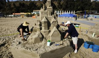 In this  April 24, 2009, file photo, architects Greg Lebon, left, and Kent Trollen sculpt a sand castle on the beach during a preview tour of the Annenberg Community Beach House in Santa Monica, Calif. Santa Monica, a sun-splashed beach city of 92,000 people not only has a famous funky old pier and miles of beautiful beaches but enough museums, art galleries, historic landmarks, and chic shopping districts to rival even that giant metropolis to its east. (AP Photo/Reed Saxon, File)