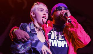 Miley Cyrus, left, joins Mike Will Made It onstage at the Fader Fort Presented by Converse during the SXSW Music Festival on Thursday, March 19, 2015 in Austin, Texas. (Photo by Jack Plunkett/Invision/AP)