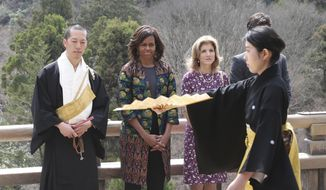U.S. first lady Michelle Obama, second from left, watches a Noh performance by local college students, with monk of Kiyomizu-dera Buddhist temple, Eigen Onishi, left, U.S. Ambassador to Japan Caroline Kennedy, second from right,  at the temple in Kyoto, western Japan, Friday, March 20, 2015. Noh is a form of classical Japanese musical drama. Kiyomizu-dera is a UNESCO World Heritage site and one of Kyoto's most famous vistas. (AP Photo/Koji Sasahara)