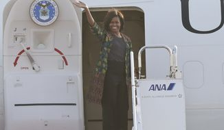 U.S. first lady Michelle Obama waves as she leaves for Cambodia after her three-day visit to Japan at Itami Airport in Osaka, western Japan Friday, March 20, 2015. (AP Photo/Koji Sasahara)