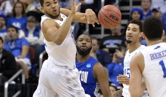 Kentucky's Karl-Anthony Towns, left, passes the ball to Kentucky's Devin Booker during the first half of an NCAA tournament second round college basketball game against Hampton in Louisville, Ky., Thursday, March 19, 2015. (AP Photo/Timothy D. Easley)