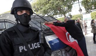 A man places a Tunisian flag onto a police car as a policeman stands guard during a demonstration two days after gunmen attacked the museum and killed scores of people in Tunis, Tunisia, Friday, March 20, 2015. (AP Photo/Christophe Ena) ** FILE **