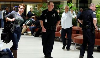 Officers guard the entrance to concourse A and B at the New Orleans International Airport, Friday, March 20, 2015, in Kenner, La. Richard White sprayed a TSA agent in the face with wasp killer then slashed a second guard with a machete before a third agent shot him three times at a security checkpoint in the New Orleans international airport Friday. (AP Photos/Jonathan Bachman)