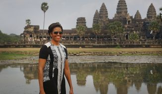 U.S. first lady Michelle Obama, takes a tour of Cambodia's famed Angkor Wat temple complex Saturday, March 21, 2015, in Siem Reap, Cambodia. Mrs. Obama on Saturday urged Cambodian students to stay in school and take advantage of their education to demand greater freedoms and more equality in their Southeast Asian country. (AP Photo/Wong Maye-E)