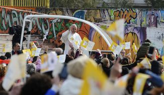Pope Francis waves from the popemobile during his visit to Scampia, suburb of Naples, Italy, Saturday, March 21, 2015. Pope Francis made an impassioned defense of the unemployed during a speech to people in the poor Neapolitan neighborhood of Scampia Saturday. (AP Photo/Salvatore Laporta)