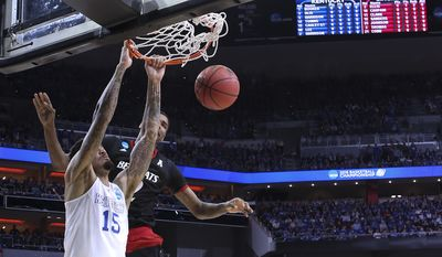 Kentucky forward Willie Cauley-Stein dunks in front of Cincinnati forward Octavius Ellis and guard Troy Caupain, right, during the first half of an NCAA tournament third round college basketball game in Louisville, Ky., Saturday, March 21, 2015. (AP Photo/David Stephenson)