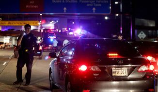 An officer directs traffic at the entrance to New Orleans International Airport, Friday, March 20, 2015, in Kenner, La. Richard White sprayed a TSA agent in the face with wasp killer then slashed a second guard with a machete before a third agent shot him three times at a security checkpoint in the New Orleans international airport Friday. (AP Photos/Jonathan Bachman)