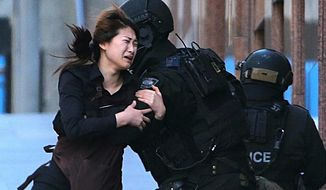 FILE - In this Dec. 15, 2014 file photo, a hostage runs to armed tactical response police officers for safety after she escaped from a cafe under siege at Martin Place in the central business district of Sydney, Australia.  For a country of just 24 million that is thousands of miles from Syria and Iraq, Australia has been unusually fertile ground for Islamic State recruiters. (AP Photo/Rob Griffith, File)