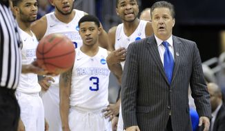 Kentucky guard Aaron Harrison, second from right, and head coach John Calipari listen to the official's explanation of a technical foul called on Harrison during the second half of an NCAA tournament college basketball game against Cincinnati in Louisville, Ky., Saturday, March 21, 2015. Kentucky won the game 64-51. (AP Photo/David Stephenson)