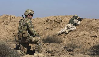 A U.S. soldier trains an Iraqi security forces member in a shooting drill in Taji, north of Baghdad, Iraq, Saturday, March 21, 2015. (AP Photo/Karim Kadim) ** FILE **