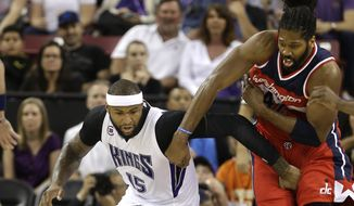 Sacramento Kings left DeMarcus Cousins and Washington Wizards forward Nene, of Brazil, scramble after the ball during the first quarter of an NBA basketball game in Sacramento, Calif., Sunday, March 22 , 2015. (AP Photo/Rich Pedroncelli)