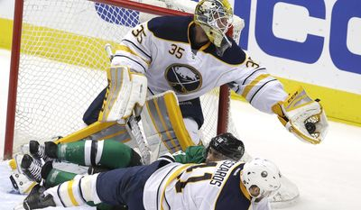 Buffalo Sabres goalie Anders Lindback (35) catches the puck as teammate defenseman Andrej Meszaros (41) knocks Dallas Stars right wing Patrick Eaves (18) off his feet during the second period of an NHL hockey game Monday, March 23, 2015, in Dallas. (AP Photo/LM Otero)