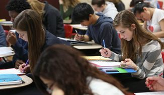 In this Thursday, March 19, 2015 file photo, students work on an exercise in Jada Callahan's Intro to Sociology 101 college course at Middleton High School in Middleton, Wis. (AP Photo/Wisconsin State Journal, Amber Arnold) ** FILE **