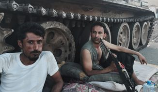 Members of a militia group loyal to Yemen's President Abed Rabbo Mansour Hadi, known as the Popular Committees, chew qat as they sit next to their tank, guarding a major intersection in Aden, Yemen, in this March 21, 2015, file photo. Once hailed by President Barack Obama as a model for fighting extremism, the U.S. counterterrorism strategy in Yemen has all but collapsed as the country descends into chaos, according to U.S. and Yemeni officials. (AP Photo/Hamza Hendawi, File)