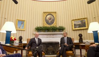 Microphones hover above Afghan President Ashraf Ghani and President Barack Obama during their meeting in the Oval Office of the White House in Washington, Tuesday, March 24, 2015. (Associated Press)