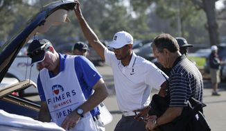 FILE - In this Feb. 5, 2015, file photo, Tiger Woods, center, loads his car after withdrawing during the first round of the Farmers Insurance Open golf tournament in San Diego. Woods was fleeing from a golf tournament in mid-round, mumbling something about improper activation of his glutes. Two weeks before the Masters he's still missing in action, though his fans have plenty of ideas on how to get his mojo back. (AP Photo/Gregory Bull, File)