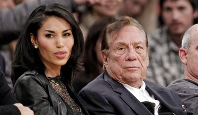 Los Angeles Clippers owner Donald Sterling, right, sits with V. Stiviano as they watch the Clippers play the Los Angeles Lakers during an NBA preseason basketball game in Los Angeles in this Dec. 19, 2011, file photo. Sterling's wife, Shelly Sterling, is going after the $2.5 million in real estate and cars her husband lavished on V. Stiviano in a trial scheduled to begin Wednesday, March 25, 2015, in Los Angeles Superior Court. (AP Photo/Danny Moloshok, File)