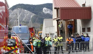 Rescue workers and security officers guard the makeshift morgue prepared for the 150 victims who died in a Germanwings plane crash in the French Alps, in Seyne-les-Alpes, France Wednesday, March 25, 2015. A cockpit voice recorder badly damaged when the German jetliner smashed into an Alpine mountainside and a crucial two-minute span when the pilot lost contact are vital clues into what caused the plane to go down, killing all 150 people on board, officials said Wednesday. (AP Photo/Christophe Ena)