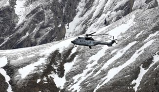 A French army helicopter heads to the Germanwings flight crash site near Seyne-les-Alpes, Wednesday, March 25, 2015, after the jetliner crashed Tuesday in the French Alps. (Associated Press)