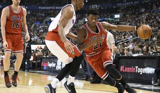 Chicago Bulls' Jimmy Butler (21) drives along the base line as Toronto Raptors' DeMar DeRozan defends during the first half of an NBA basketball game, Wednesday, March 25, 2015 in Toronto. (AP Photo/The Canadian Press, Frank Gunn)