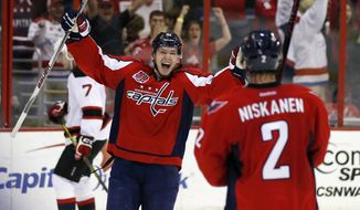 Washington Capitals center Evgeny Kuznetsov (92), from Russia, comes to celebrate with defenseman Matt Niskanen (2) after Niskanen's goal to win in the overtime period of an NHL hockey game against the New Jersey Devils, Thursday, March 26, 2015, in Washington. The Capitals won 3-2 in overtime. (AP Photo/Alex Brandon)