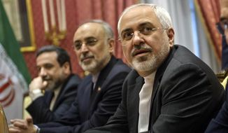 Iranian Foreign Mohammad Minister Javad Zarif, right, waits for the start of a meeting with a U.S. delegation at a hotel in Lausanne Switzerland on Thursday March 26, 2015, during negotiations on the Iranian nuclear program. (AP Photo/Brendan Smialowski)