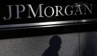 In this Nov. 19, 2013, file photo, the shadow of a pedestrian is cast under a sign in front of JPMorgan Chase & Co. headquarters in New York. (AP Photo/Seth Wenig, File)