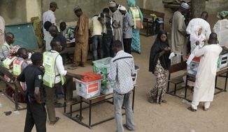 A police officer stand guards as people cast their votes during Presidential and National assembly election in Yola, Nigeria Saturday, March 28, 2015. Nigerians went to the polls Saturday in presidential elections which analysts say will be the most tightly contested in the history of Africa's richest nation and its largest democracy. (AP Photo/Sunday Alamba)