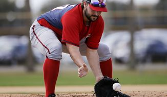 Washington Nationals pitcher Tanner Roark plays a ground ball during a drill at a spring training baseball workout, Sunday, Feb. 22, 2015, in Viera, Fla. (AP Photo/David Goldman)