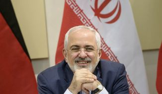 Iranian Foreign Minister Javad Zarif smiles before a meeting on Iran's nuclear program with Britain, Russia, China, France, Germany, European Union and the U.S. officials at the Beau Rivage Palace Hotel in Lausanne, Switzerland Monday, March 30, 2015. (AP Photo/Brendan Smialowski, Pool)