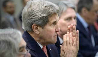 U.S. Secretary of State John Kerry waits with others before a meeting with Britain, Russia, China, France, Germany, European Union and Iranian officials at the Beau Rivage Palace Hotel in Lausanne, Switzerland Monday, March 30, 2015, during Iran nuclear talks. (AP Photo/Brendan Smialowski, Pool)