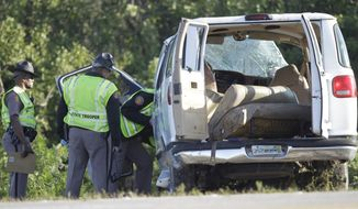 Florida Highway investigators examine a van that crashed into canal at the intersection of US 27 and State Road 78 West, Monday, March 30, 2015, near Moore Haven, Fla. Eight people were killed and 10 injured when the church van ran through a stop sign, crossed all four lanes of a rural highway and crashed into in a canal.  (AP Photo/Luis M. Alvarez)