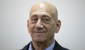 Former Israeli Prime Minister Ehud Olmert smiles as he waits in a court room in Jerusalem's District Court on Monday, March 30, 2015. The court later found Olmert guilty of accepting bribes in a retrial of corruption charges, (AP Photo/Abir Sultan, Pool)