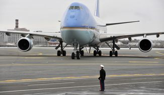 A marine stands at attention on the tarmac as Air Force One. with President Barack Obama and first lady Michelle Obama aboard, arrives at Logan Airport in Boston Monday, March. 30, 2015. Obama is speaking at the dedication for the $79 million Edward M. Kennedy Institute for the United States Senate, which sits next to the presidential library of Kennedy's brother, John F. Kennedy. (AP Photo/Josh Reynolds)