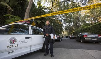 An officer stands outside a home in the Hollywood Hills area of Los Angeles, Tuesday, March 31, 2015. Police say a man was found dead at the home of Andrew Getty, heir to Getty oil fortune. (AP Photo/Ringo H.W. Chiu)