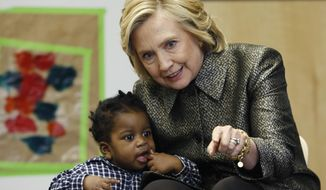 Hillary Rodham Clinton talks to a youngster during a visit to an early childhood development center in the Brooklyn borough of New York, Wednesday, April 1, 2015. Clinton and New York City first lady Chirlane McCray joined forces with the city's deputy mayor in announcing a program to get parents to talk to their young children to enhance their development. (AP Photo/Kathy Willens, Pool})