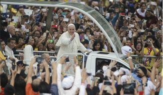 Crowds cheer as Pope Francis passes by during his meeting with the youth at the University of Santo Tomas in Manila, Philippines on Sunday, Jan. 18, 2015. Francis drew a huge crowd earlier Sunday when he addressed young people at Manila's Catholic university, coming close to tears himself when he heard two young children speak of their lives growing up poor and on the streets. (AP Photo/Aaron Favila)