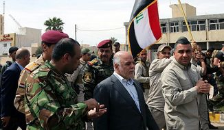 """Iraqi Prime Minister Haider al-Abadi tours the city of Tikrit after it was retaken by the security forces in Baghdad, Iraq, Wednesday, April 1, 2015. Iraq declared a """"magnificent victory"""" over the Islamic State group in Tikrit, a key step in driving the militants out of their biggest strongholds. (AP Photo)"""