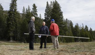Gov. Jerry Brown, center, talks Mark Cowin, left, director of the California Department of Water Resources, and Frank Gehrke, chief of the California Cooperative Snow Surveys Program for the DWR, near Echo Summit, Calif., Wednesday, April 1, 2015. (AP Photo/Rich Pedroncelli)