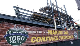 In this Tuesday, March 24, 2015, photo, renovations to Wrigley Field's left field bleachers and the addition of a jumbo video screen continue in Chicago. When fans arrive for the Chicago Cubs' baseball season opener Sunday, April 5, 2015, against the archrival St. Louis Cardinals, they will get their first real look at the most visible phase of a massive renovation project. Just like in 1937, there will be new bleachers and a new brick outfield wall, just recently adorned with ivy. Even the centerpiece of the project, a brand new Jumbotron, will harken back to the day when Depression-era fans beheld a state-of-the-art manual scoreboard. (AP Photo/Charles Rex Arbogast)