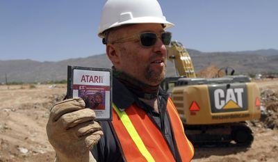 """FILE - In this April 26, 2014 file photo, film director Zak Penn shows a box of a decades-old Atari """"E.T. the Extra-Terrestrial"""" game found in a dumpsite in Alamogordo, N.M. A documentary on Atari's decline and a decades-old urban legend on the secret dumping of the """"E.T."""" game in the New Mexico desert is airing on Netflix. """"Atari: Game Over"""" was released on the streaming service late Wednesday, April 1, 2015, and details the demise of gaming giant Atari.   (AP Photo/Juan Carlos Llorca, File)"""